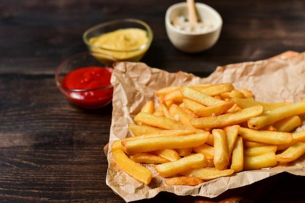 Frieten met ketchup, mosterd en zout. fastfoodlunch op een houten tafel. zakelijk lunchmenu, fast food bezorging