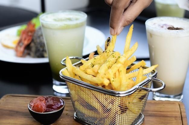 Frietjes in mandje met sojasaus en een drankje als bijgerecht