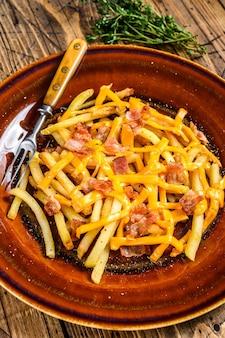 Frietjes met gesmolten cheddar kaas en bacon geserveerd op een rustiek bord. houten achtergrond. bovenaanzicht.