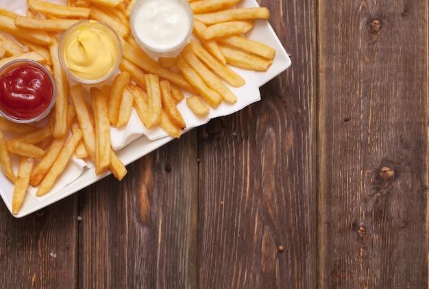 Frietjes met saus op houten tafel.