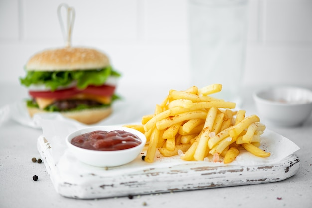 Frietjes met tomatenketchup en hamburger op witte tafel