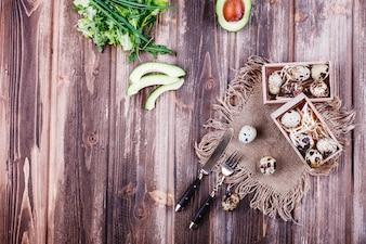 Fris en gezond eten, eiwitten. Kwarteleitjes in houten kist staan op de rustieke tafel