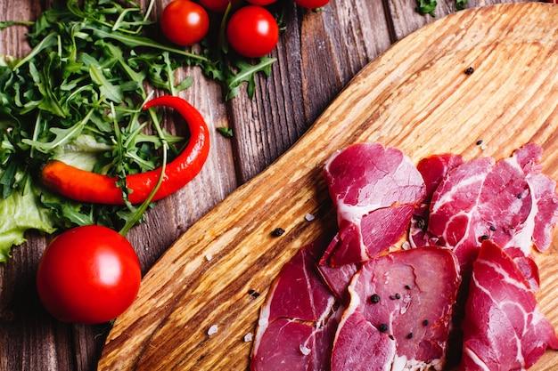 Fris en gezond eten. gesneden rood vlees ligt op de houten tafel met rucola
