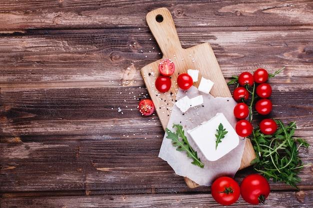 Fris en gezond eten. heerlijk italiaans diner. verse kaas geserveerd op een houten bord