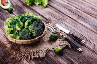 Fris en gezond eten. Houten kom met broccoli, spruitjes, olijfolie, groene peper