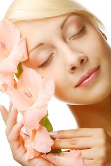 Fris gezicht met gladiolenbloemen in haar handen