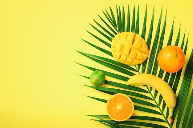 Fris oranje, banaan, ananas, mango smoothie en sappige vruchten op palmbladeren op gele achtergrond. detox zomerdrankje. vegetarisch concept.