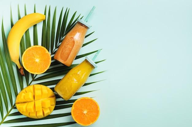 Fris oranje, banaan, ananas, mango smoothie en sappige vruchten op palmbladeren over blauwe achtergrond. detox zomerdrankje.