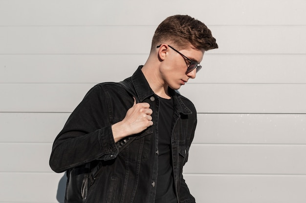 Fris portret modieuze jonge man in stijlvol denim zwart jasje in trendy zonnebril