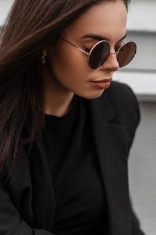 Fris portret van schattige mooie jonge vrouw in ronde modieuze zonnebril in zwarte stijlvolle blazer met sexy lippen buiten in de stad. aantrekkelijk meisje mannequin in casual elegante zakelijke kleding.