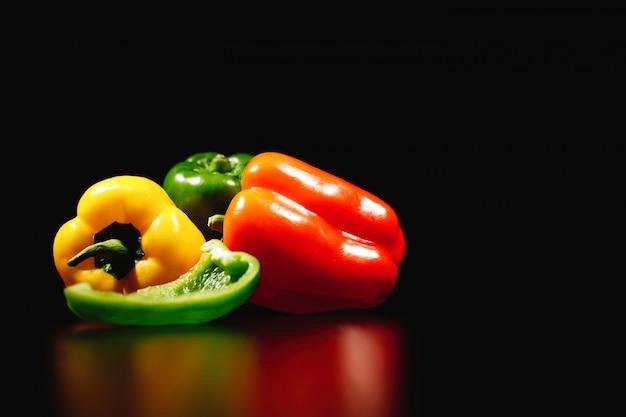 Fris, smakelijk en gezond eten. rode, gele en groene paprika's die op zwarte achtergrond worden geïsoleerd