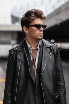 Fris stijlvol portret van een jonge man hipster in stijlvolle zonnebril met een modieus kapsel in trendy zwarte kleding in de straat. amerikaanse knappe jongen model poseren buitenshuis. trendy herenkleding.