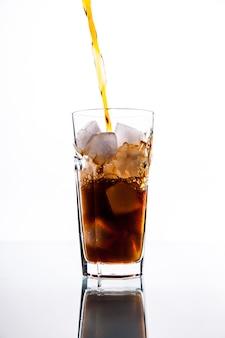 Frisdrank. cola giet van fles naar glas