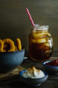 Frisdrank omgeven door uienringen en sauzen