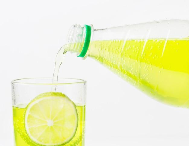 Frisdrank wordt met limoen in glas gegoten