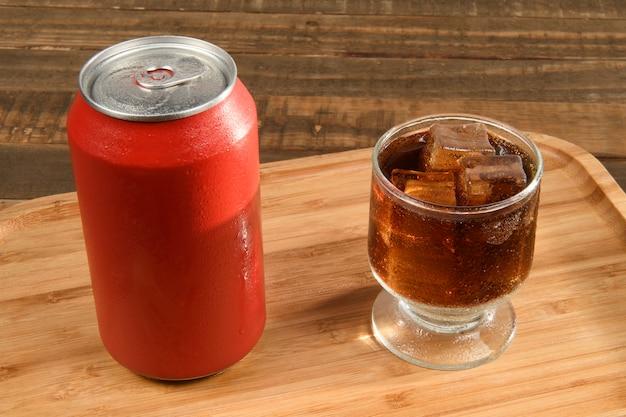 Frisdrankblikje met een glas vol ijs en drankje op bamboe dienblad