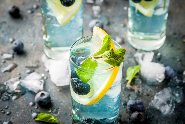 Frisdrankjes voor de zomer, blueberry-limonade of mojito-cocktail met citroen, verse bosbessen en munt, sdark blue stone copyspace
