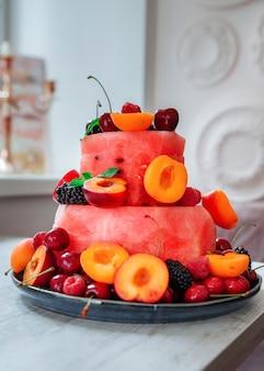 Frisheid fruit- en bessensalade in de vorm van een cake versierd met muntblaadjes zomerdessert