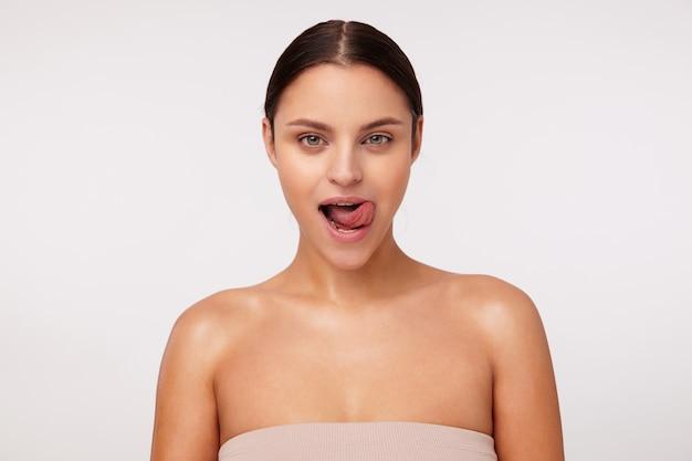 Frisky jonge aantrekkelijke donkerharige vrouw met natuurlijke make-up die speels kijkt en haar tong uitsteekt, gekleed in beige top tijdens het poseren