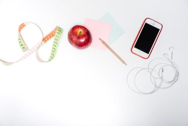 Frisse appel; meetlint; zelfklevende notities en smartphone op witte achtergrond