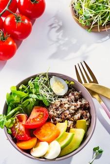 Frisse gezonde salade met quinoa, cherrytomaten en gemengde greens, avocado, ei en micro greens op marmer