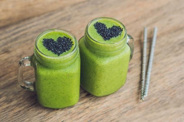 Frisse groene smoothie met banaan en spinazie met hart van sesamzaadjes. liefde voor een gezond raw food concept