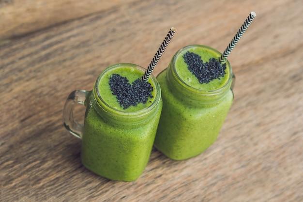 Frisse groene smoothie met banaan en spinazie met hart van sesamzaadjes