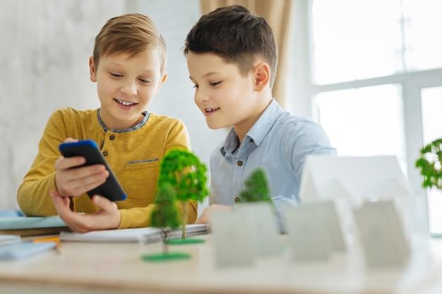 Frisse ideeën. aangename pre-tienerjongens die aan tafel zitten en hun mobiele telefoon gebruiken terwijl ze op zoek zijn naar nieuwe ideeën voor hun ecologieproject