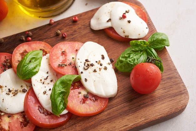 Frisse italiaanse salade antipasto genaamd caprese met buffelmozzarella, gesneden tomaten en basilicum met olijfolie. ingrediënten voor vegetarische caprese salade. italiaans eten. bovenaanzicht. rustieke stijl.