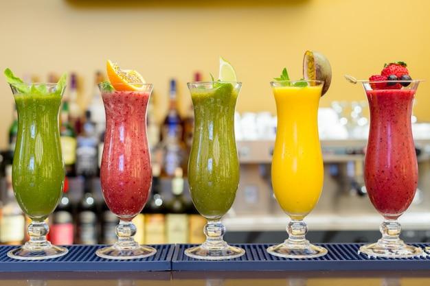 Frisse kleurensappen smoothie violet groen geel oranje rood tropische vruchten