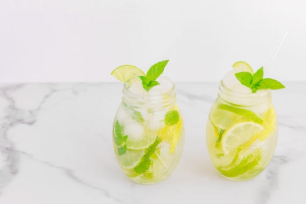 Frisse koele detox waterdrank met munt en citroen. twee glazen limonade met munt. concept van goede voeding en gezond eten. fitness dieet.