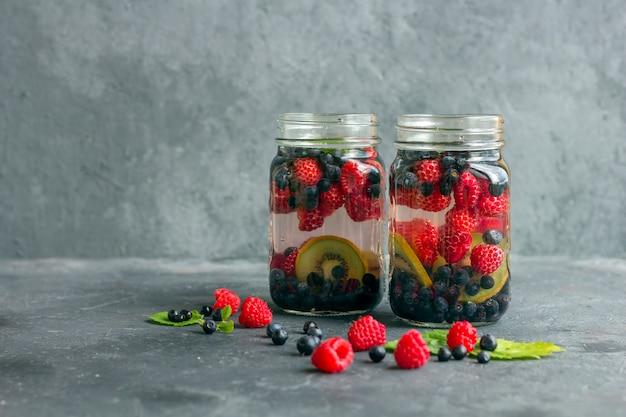 Frisse koele detoxdrank met frambozen, bosbessen en kiwi in de mok van de metselaarkruik. limonade in een glas met een munt. het concept van goede voeding en gezond eten. fitness dieet. kopieer ruimte voor tex