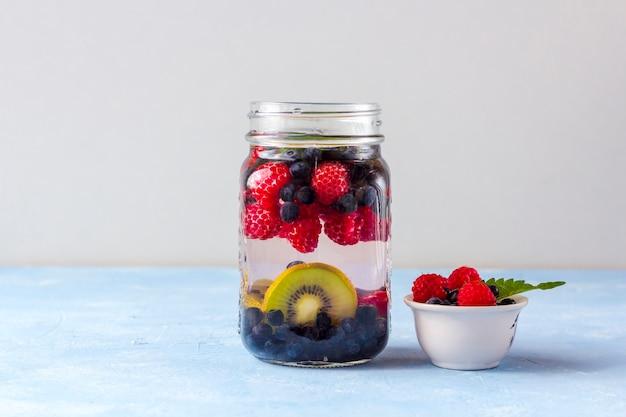 Frisse koele detoxdrank met frambozen, bosbessen en kiwi in de mok van de metselaarkruik. limonade in een glas met een munt. het concept van goede voeding en gezond eten. fitness dieet