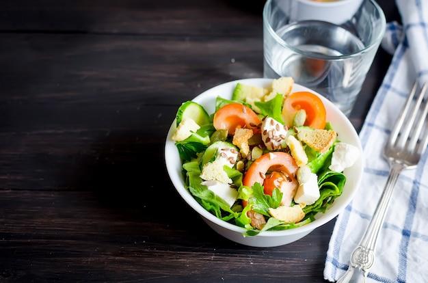 Frisse lichtgroene salade met komkommer, sla, avocado, tomaten en glaswater op een houten tafel. gezonde levensstijl concept.