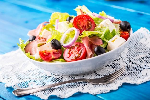 Frisse mediterrane salade olijven tomaten parmezaanse kaas en prosciutto