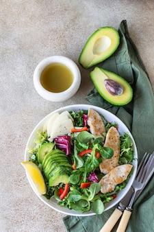 Frisse mixsalade met gegrilde kipfilet, avocado, appel en paprika en olijfolie en citroendressing.