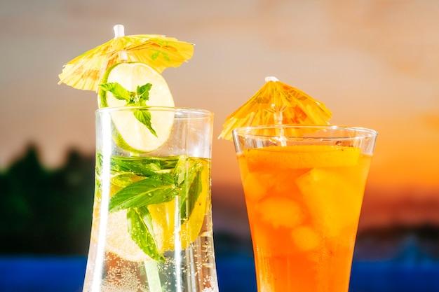 Frisse oranje drankjes met ijsblokjes in geslepen limoenmunt