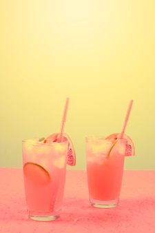 Frisse roze alcoholische cocktail met grapefruit; schijfje citroen en ijsblokjes tegen gele achtergrond