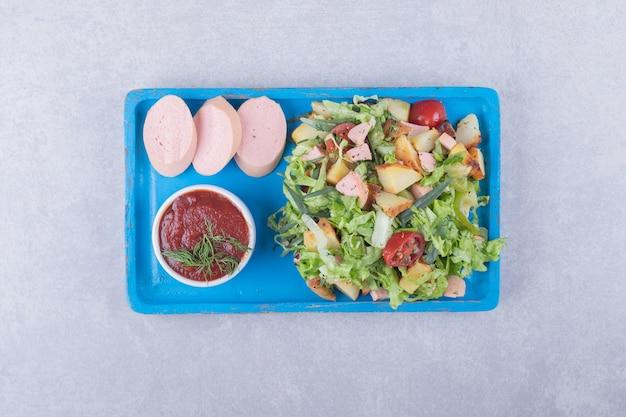Frisse salade en gekookte worstjes op blauw bord.