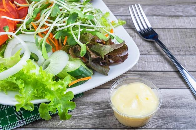 Frisse salade en saladedressing voor de gezondheid op een houten tafel
