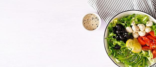 Frisse salade met avocado, tomaat, olijven en mozzarella in een kom