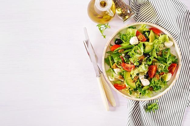 Frisse salade met avocado, tomaat, olijven en mozzarella in een kom.