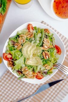 Frisse salade met avocado, walnoten en tomaten op tafel