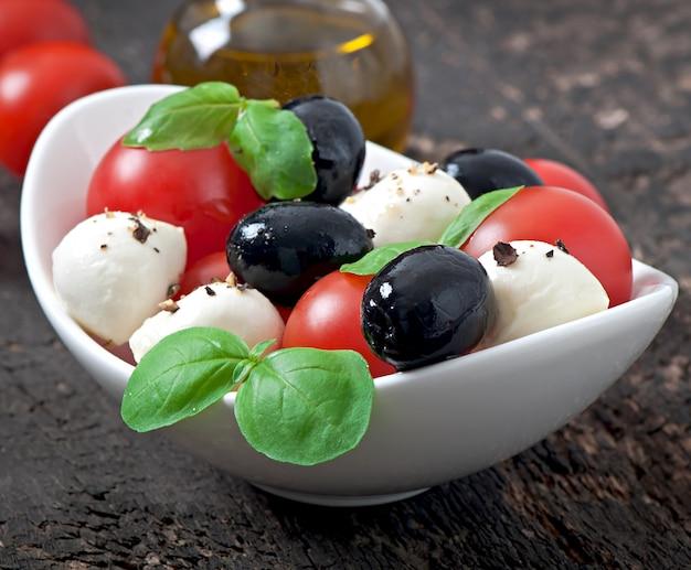Frisse salade met cherrytomaten, basilicum, mozzarella en zwarte olijven.