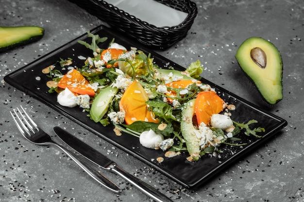 Frisse salade met fruit en greens op donkere canvasachtergrond. gezond eten.