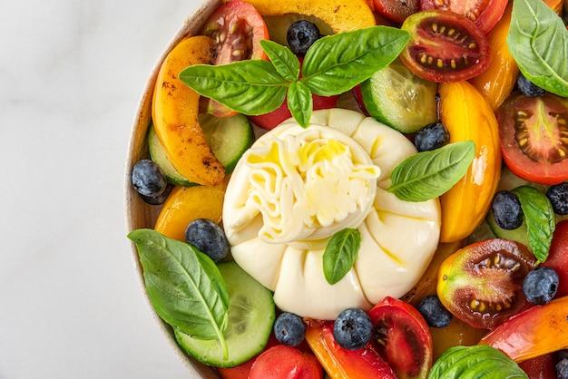 Frisse salade met gegrilde perziken burrata kaas bosbessen en groenten op een bord