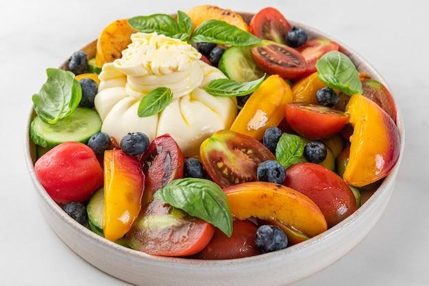 Frisse salade met gegrilde perziken burrata kaas bosbessen groenten en basilicum in een bord