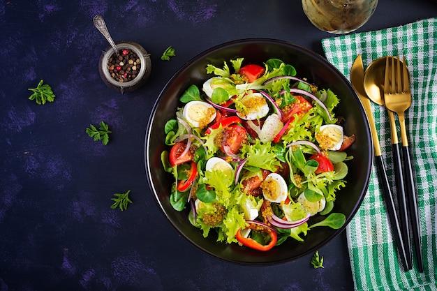 Frisse salade met groenten, tomaten, rode uien, sla en kwarteleitjes. gezond voedsel en dieetconcept. vegetarisch eten. bovenaanzicht, boven het hoofd