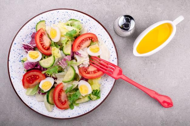 Frisse salade met groententomaten, komkommers, meng slablaadjes, eieren en olijfolie.