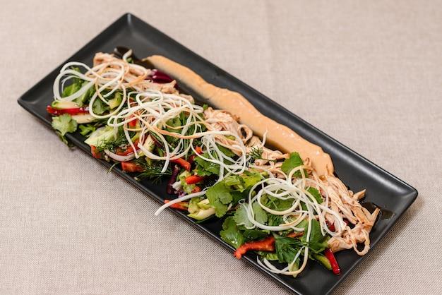 Frisse salade met kalkoen op een zwarte plaat verse groenten en kaas